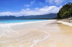 Нежные волны вымывают мягкий песок пляжа Вайманало на восточном берегу Оаху